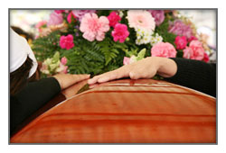 Hands rest on a coffin with flowers at a funeral viewing services in Augusta, ME